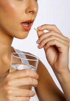 Woman Holding Glass of Water and Green Coffee Supplement