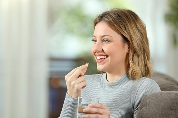 Woman Holding Glass of Water and Pill