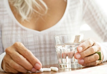Woman with Glass of Water and Joint Supplements
